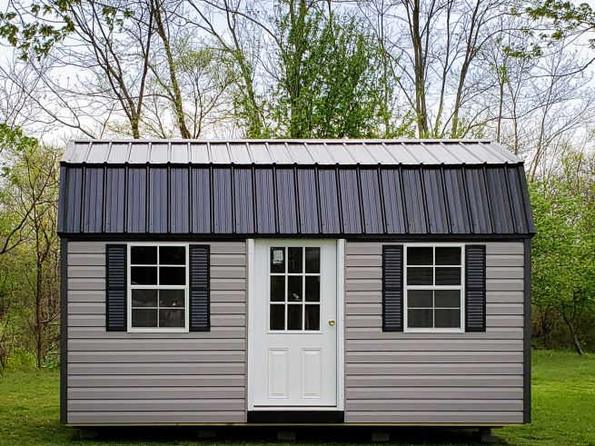 A portable building in Kentucky with vinyl siding and a black metal roof