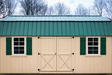 A portable building in Kentucky with painted wood siding and a green metal roof