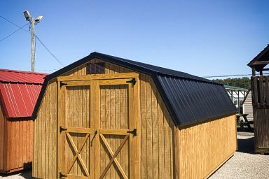 A portable building in Kentucky with wooden siding and a black metal roof