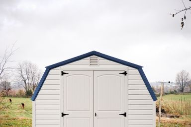 A portable building in Tennessee with vinyl siding and a blue metal roof