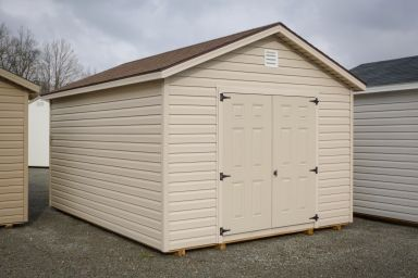 A shed in Kentucky with vinyl siding, double doors, and a shingle roof