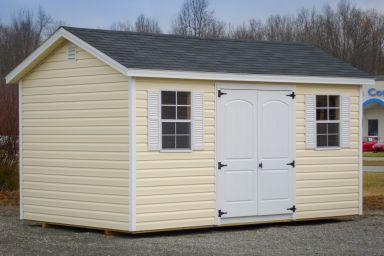 A shed in Kentucky with vinyl siding, windows with shutters, and a shingle roof