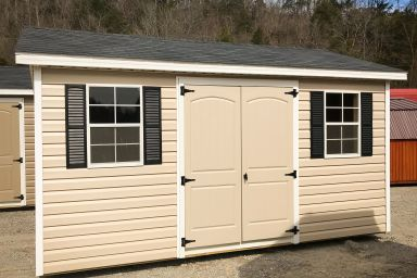 A vinyl shed with double doors, windows, and shutters