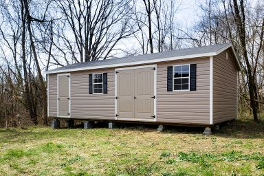 A vinyl shed in Kentucky with double doors, windows, and shutters