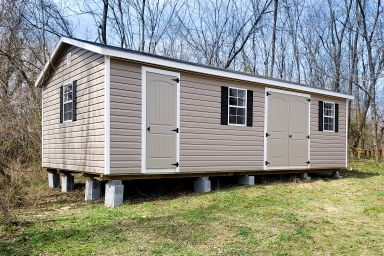 A vinyl shed in Kentucky with double doors, windows, and black shutters
