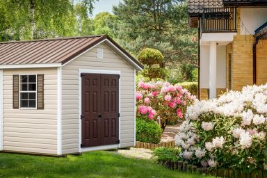 A shed in Tennessee with vinyl siding and a brown metal roof