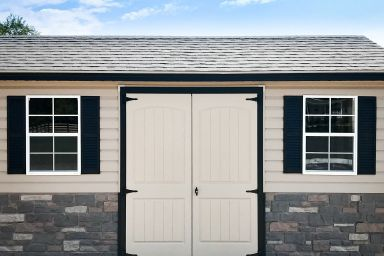 A customized shed in Tennessee with vinyl siding and double doors