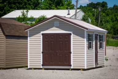 A garden shed in Kentucky with vinyl siding, double doors, and a brown metal roof