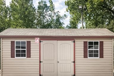 A discounted garden shed in Tennessee with vinyl siding, double doors, and a shingle roof