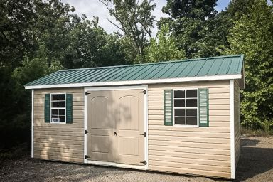 A garden shed in Tennessee with vinyl siding, double doors, and a green metal roof