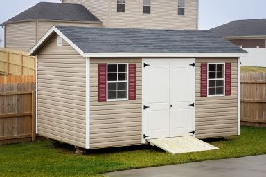 A garden shed in Tennessee with vinyl siding, double doors, and windows with shutters