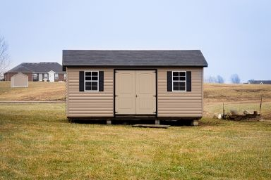 A garden shed in Tennessee with vinyl siding, double doors, windows, and a shingle roof