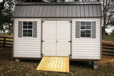 A lofted garden shed in Tennessee with vinyl siding, double doors, and a black metal roof