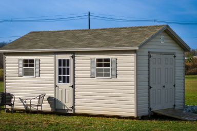 A storage shed in Kentucky with vinyl siding, double doors, and a shingle roof