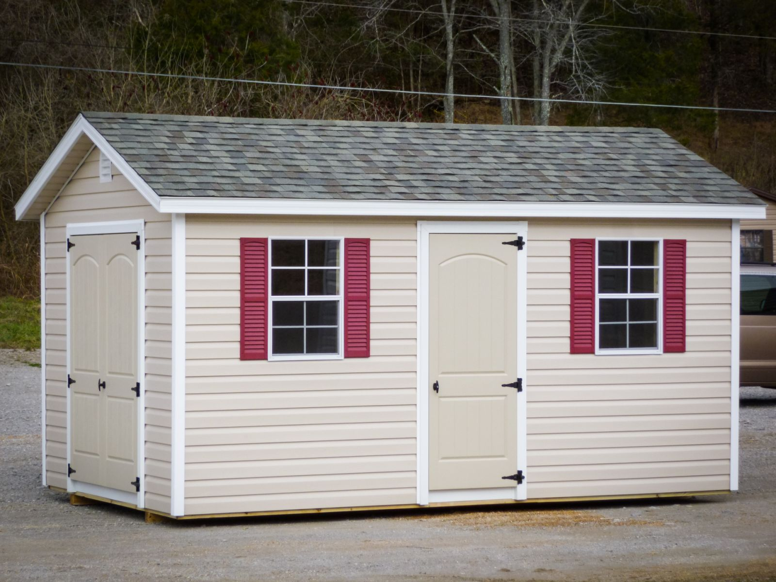A storage shed in Kentucky with vinyl siding, double doors, and windows with red shutters