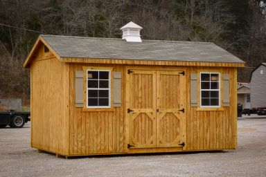 A storage shed in Kentucky with wooden siding, double doors, and a shingle roof with a cupola