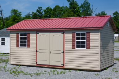 A storage shed in Kentucky with vinyl siding, double doors, and a red metal roof