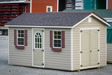 A storage shed in Kentucky with vinyl siding, double doors, and windows with flowerboxes