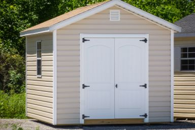 A storage shed in Tennessee with vinyl siding, double doors, and a brown shingle roof