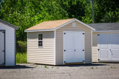 A storage shed in Tennessee with brown vinyl siding, double doors, and a brown shingle roof