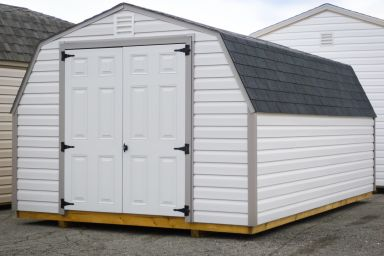 A portable shed in Kentucky with white vinyl siding, a shingle roof, and double doors