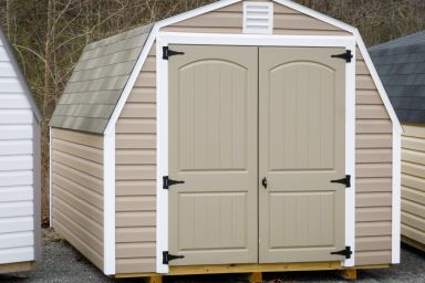 A barn-style portable shed in Kentucky with vinyl siding, a shingle roof, and double doors