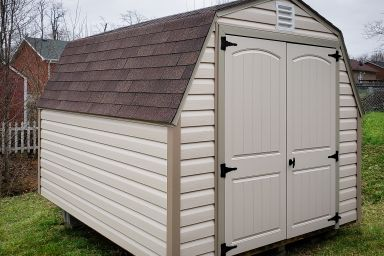 A barn-style portable shed in Tennessee with vinyl siding, a shingle roof, and double doors