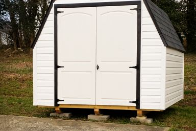A portable shed in Tennessee with vinyl siding, a black shingle roof, and double doors
