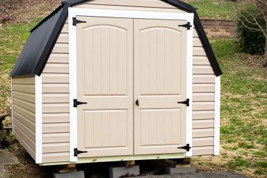 A barn-style portable shed in Tennessee with vinyl siding, a black metal roof, and double doors