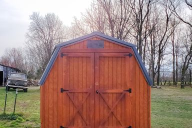 A portable shed in Tennessee with wooden siding, a metal roof, and double doors