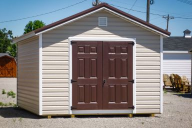 A storage shed in Tennessee with vinyl siding, brown double doors, and a brown metal roof