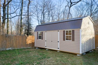 An outdoor shed in Kentucky with vinyl siding and a metal roof