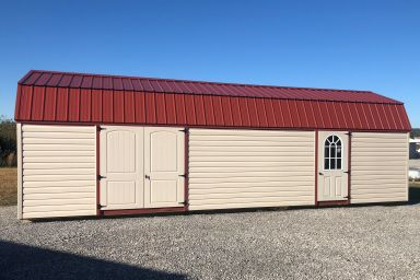 A barn-style outdoor shed in Kentucky with vinyl siding and a red metal roof