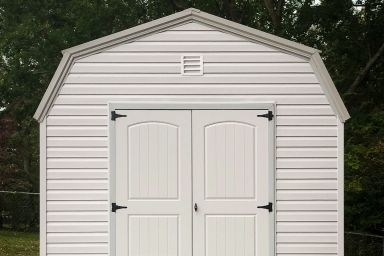 An outdoor shed in Kentucky with white vinyl siding and a metal roof