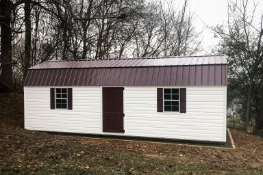 An outdoor shed in Kentucky with vinyl siding, two windows, and a metal roof