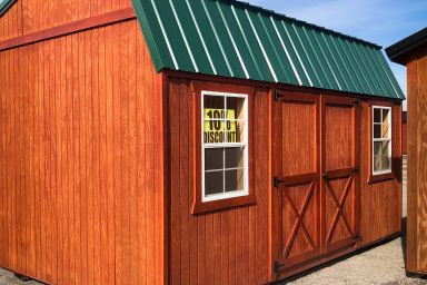 A discounted outdoor shed in Kentucky with wooden siding, two windows, and a green metal roof