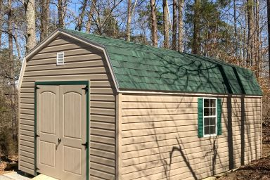 An outdoor shed in Kentucky with vinyl siding, two windows, and a green shingle roof