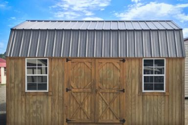 An outdoor shed in Tennessee with wooden siding, double doors, and a metal roof