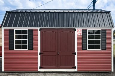 A discounted outdoor shed in Tennessee with red vinyl siding, double doors, and a metal roof