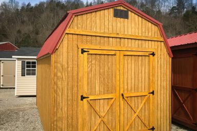 An outdoor shed in Tennessee with wooden siding, double doors, and a red metal roof