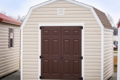 A barn-style storage building in Kentucky with vinyl siding and brown double doors