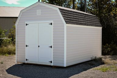 A storage building in Kentucky with vinyl siding and a shingle roof