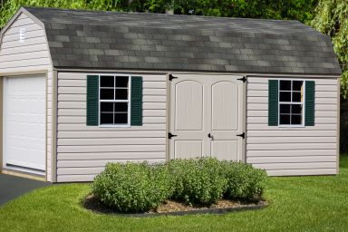 A barn-style storage building in Kentucky with vinyl siding and two windows with shutters
