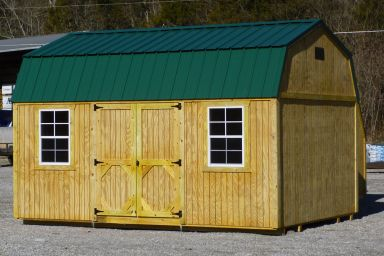 A prefab lofted storage building in Kentucky with wood siding and double doors