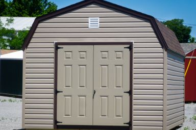 A prefab storage building in Kentucky with brown vinyl siding and double doors