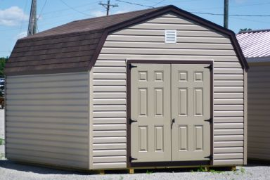 A storage building in Tennessee with vinyl siding and a brown shingle roof