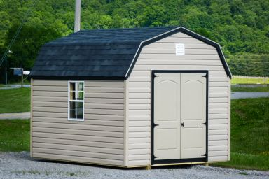 A prefab storage building in Tennessee with vinyl siding and a black shingle roof