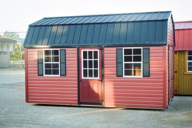 A vinyl storage building in Tennessee with red siding and two windows with shutters