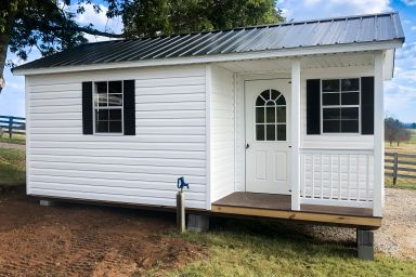 A prefab cabin in Kentucky with vinyl siding and a corner porch
