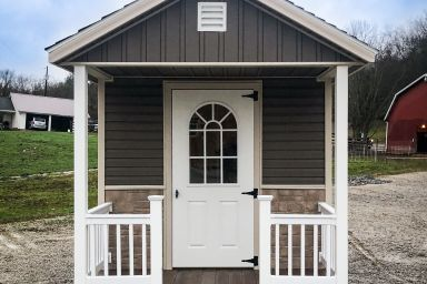 A prefab cabin in Kentucky with custom vinyl siding and a front porch